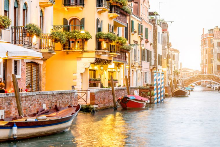 Small romantic water canal with restaurants in Dorsoduro region in Venice
