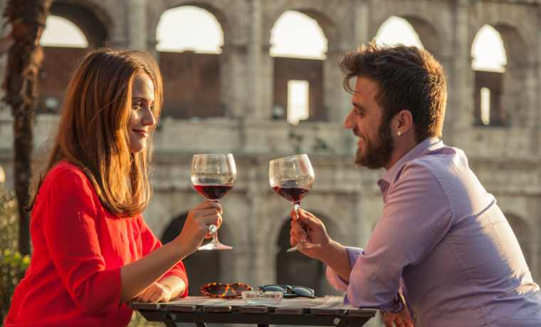 Couple drinking glass of red wine at restaurant table in front of the Colosseum, Rome