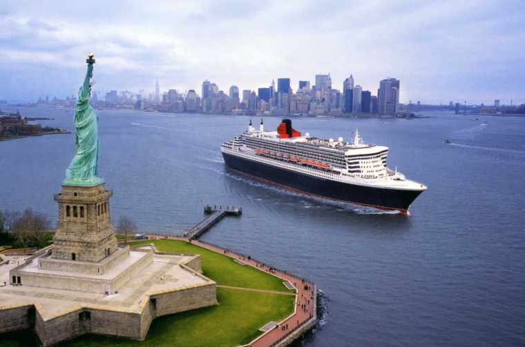 Cunard cruise holiday sailing past the statue of liberty in New York