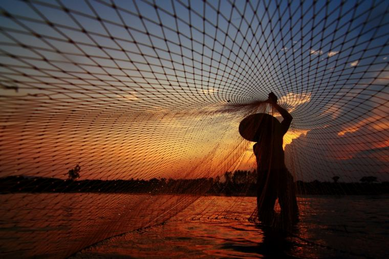 Fisherman with a net on the Mekong River