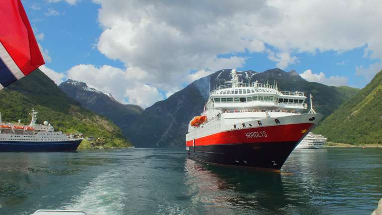 MS Nordlys sailing in beautiful Norwegian fjord alongside other ships
