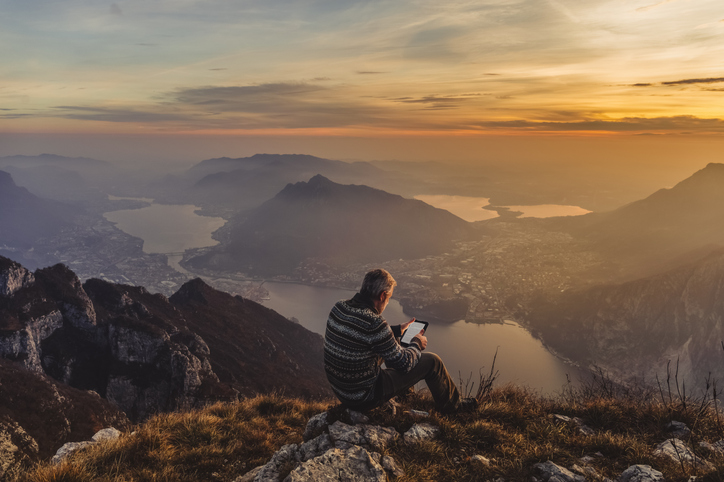 Man hiker solo reading on tablet device