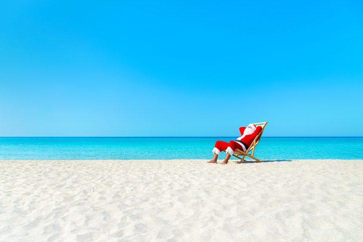 Christmas Santa Claus resting on deckchair at ocean sandy beach