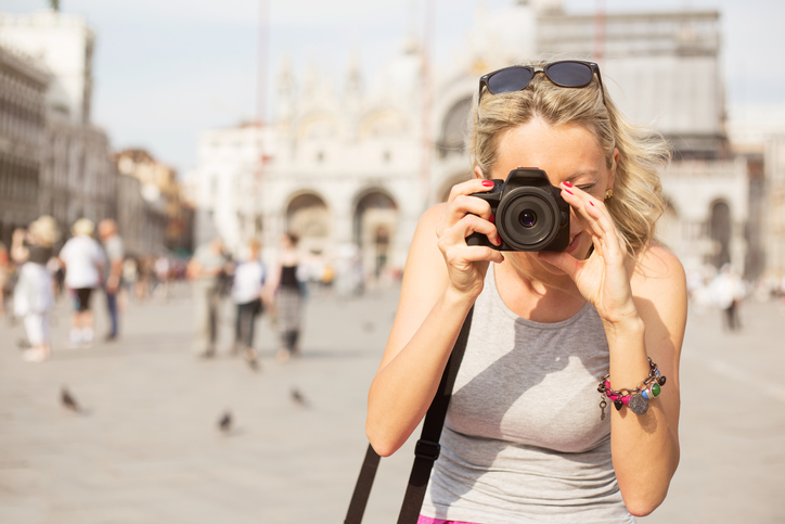 Young tourist taking photos in Venice