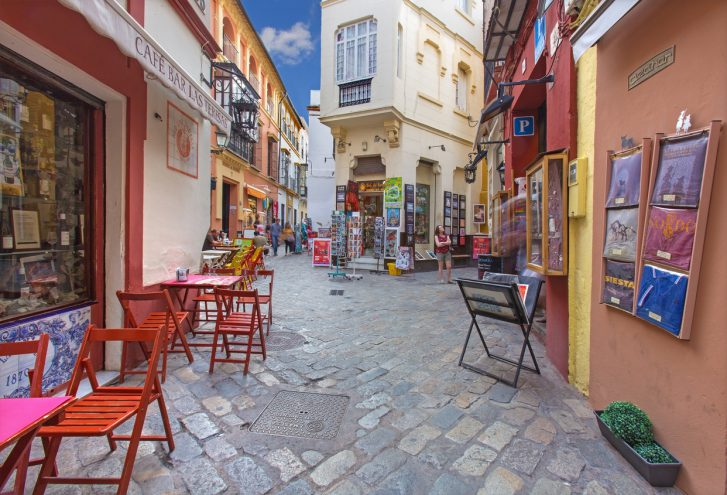 Seville, Spain - Little streets with the shops and restaurants in the Santa Cruz district - Calle Ximenez de Enciso street.