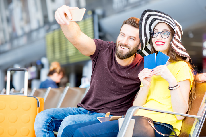 Young happy couple making selfie photo with phone at the waiting hall of the airport during their summer vacation
