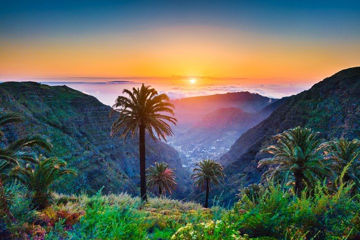 Amazing tropical scenery with palm trees and mountains at sunset