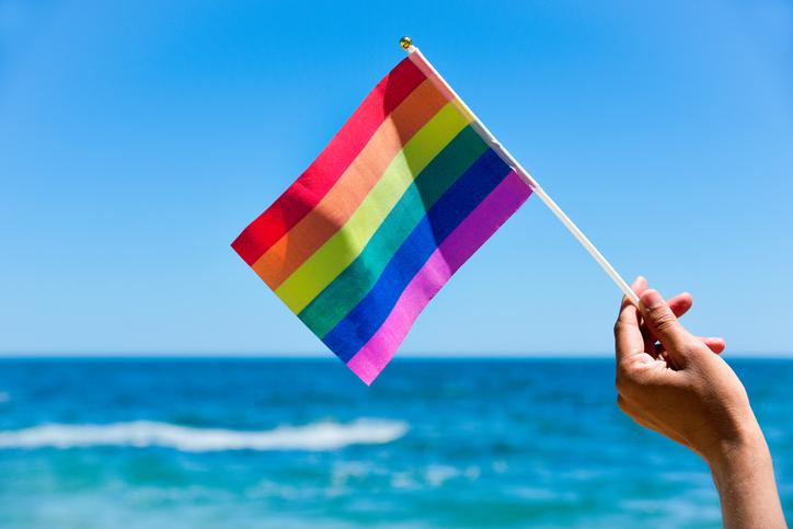 Same sex marraige, man waving a small rainbow flag