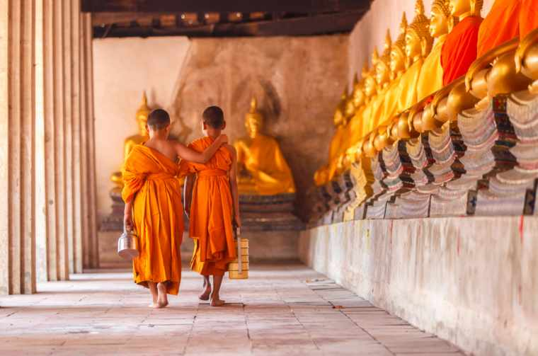 Two novices walking return and talking in old temple, Cambodia