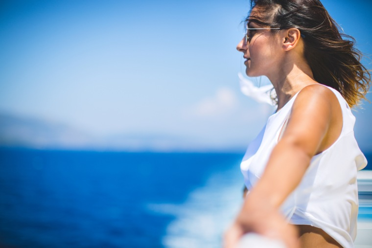 Young woman on windy cruise ship