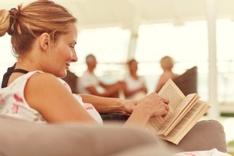 Woman relaxing on board and reading a book