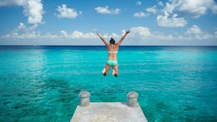 Woman jumping in the Caribbean sea on a Royal Caribbean shore excursion
