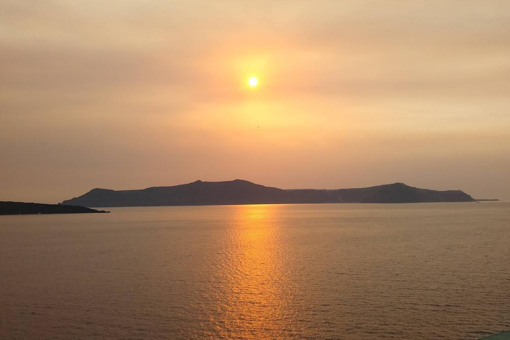 Sunset over Santorini as we sail away completes the day